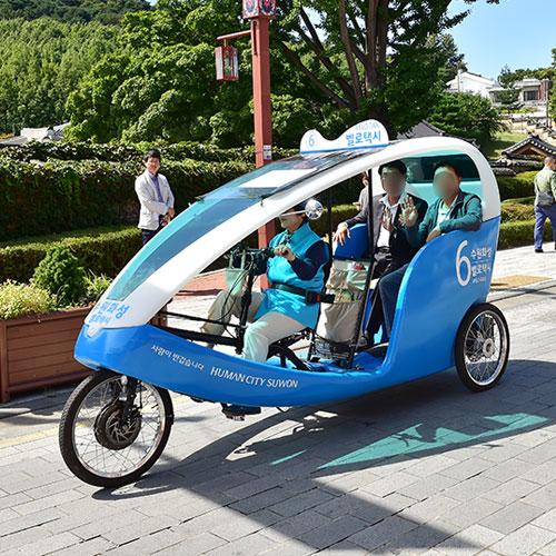 수원화성 자전거 택시를 타고 행궁길을 지나고 있는 모습